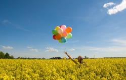 Giovane donna con gli aerostati sul campo di canola. Immagini Stock Libere da Diritti