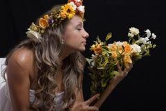 Giovane donna con gli occhi chiusi, odorando un mazzo dei fiori immagine stock