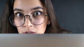 Giovane donna con gli occhi di vetro che guardano dietro il monitor, fine su con la riflessione stock footage
