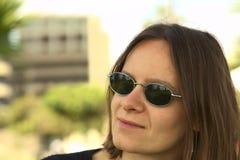 Giovane donna con gli occhiali da sole Immagini Stock