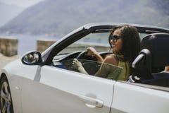 Giovane donna con gli occhiali da sole che guidano il suo automobi superiore convertibile fotografie stock