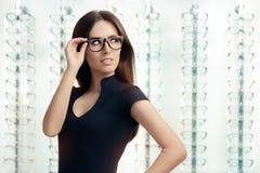 Giovane donna con gli occhiali in deposito ottico Fotografia Stock Libera da Diritti