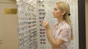 Giovane donna con gli occhiali in deposito ottico Vetri d'uso della bella ragazza nel negozio dell'ottico stock footage