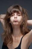 Giovane donna con i capelli di Brown che fanno un fronte fotografie stock