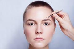 Giovane donna con i capelli di scarsità che colgono le pinzette delle sopracciglia vicino su Immagine Stock