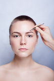 Giovane donna con i capelli di scarsità che colgono le pinzette delle sopracciglia vicino su Fotografie Stock