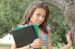 Giovane donna con i dispositivi di piegatura fotografia stock
