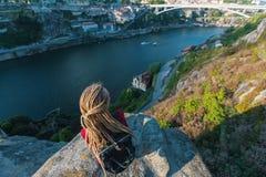 Giovane donna con i dreadlocks biondi che si siedono su un'alta scogliera sopra il fiume Corsa Fotografia Stock