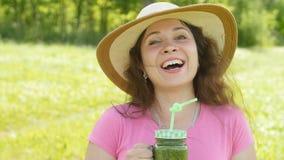 Giovane donna con i frullati di verdure verdi nel parco stock footage