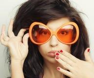 Giovane donna con i grandi occhiali da sole arancio Immagini Stock