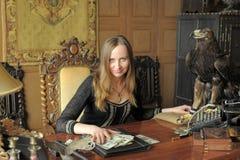 Giovane donna con i lotti dei dollari nelle sue mani ed aquila sulla tavola Fotografie Stock