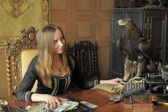Giovane donna con i lotti dei dollari nelle sue mani ed aquila sulla tavola Fotografia Stock Libera da Diritti