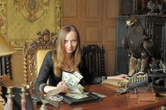 Giovane donna con i lotti dei dollari nelle sue mani ed aquila sulla tavola Fotografia Stock