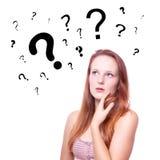 Giovane donna con i punti interrogativi Immagini Stock
