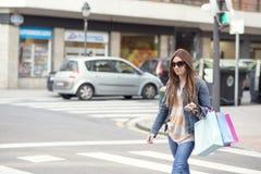 Giovane donna con i sacchetti della spesa attraverso la via. Fotografie Stock