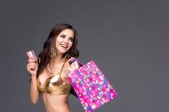 Giovane donna con i sacchetti della spesa e la carta di credito sopra Fotografia Stock