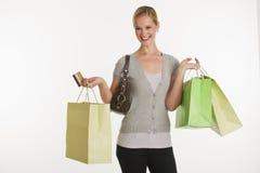 Giovane donna con i sacchetti di acquisto e la carta di credito Fotografie Stock