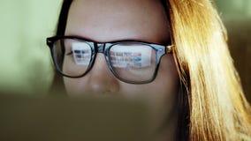 Giovane donna con i vetri che esaminano monitor stock footage