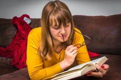 Giovane donna con i vetri che legge un libro Fotografie Stock