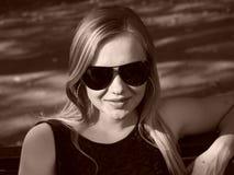 Giovane donna con i vetri di sole nella seppia Fotografia Stock