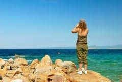 Giovane donna con il binocolo immagine stock