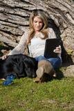 Giovane donna con il cane nero di Labrador in parco Immagine Stock
