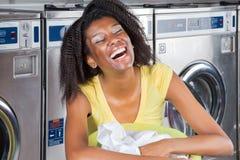 Giovane donna con il canestro di vestiti alla lavanderia automatica Fotografie Stock