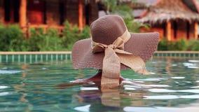Giovane donna con il cappellino da sole dalla parte posteriore nella piscina archivi video