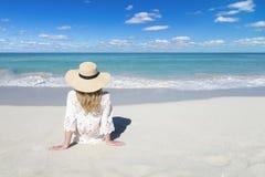 Giovane donna con il cappello rilassarsi sulla spiaggia Sabbia bianca, cielo nuvoloso blu e mare del cristallo della spiaggia tro fotografia stock libera da diritti