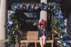 Giovane donna con il cappello rosso messo su un banco d'oscillazione a Londra immagine stock