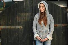 Giovane donna con il cappuccio sopra davanti alla vecchia porta fotografie stock libere da diritti