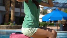 Giovane donna con il caso rosa vicino alla piscina in hotel Concetto di vacanza di viaggio video d archivio