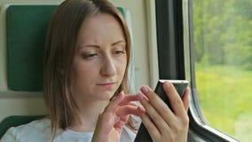 Giovane donna con il cellulare che si siede sul treno archivi video