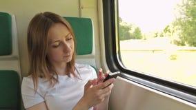 Giovane donna con il cellulare che si siede sul treno video d archivio