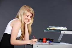 Giovane donna con il compito scolastico Immagine Stock