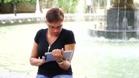 Giovane donna con il computer della compressa che si siede nel parco della città archivi video
