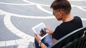 Giovane donna con il computer della compressa che si siede nel parco della città video d archivio