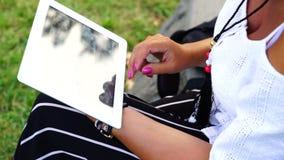 Giovane donna con il computer della compressa che si siede nel parco della città stock footage