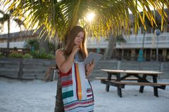 Giovane donna con il computer della compressa sulla spiaggia immagine stock libera da diritti