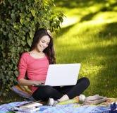 Giovane donna con il computer portatile Immagine Stock