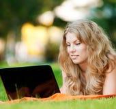 Giovane donna con il computer portatile alla sosta Fotografie Stock