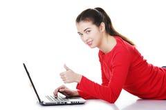 Giovane donna con il computer portatile che gesturing bene Fotografie Stock