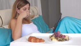 Giovane donna con il computer portatile che mangia prima colazione a letto a casa e che beve caffè video d archivio