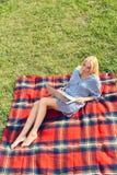 Giovane donna con il computer portatile che si siede nell'erba verde del prato Fotografia Stock Libera da Diritti