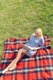 Giovane donna con il computer portatile che si siede nell'erba verde del prato Fotografie Stock Libere da Diritti