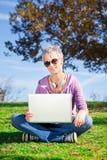 Giovane donna con il computer portatile che si siede sull'erba Fotografia Stock