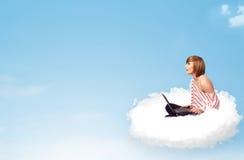 Giovane donna con il computer portatile che si siede sulla nuvola con lo spazio della copia Immagini Stock