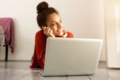 Giovane donna con il computer portatile che si trova sul pavimento e sul pensiero Fotografia Stock Libera da Diritti