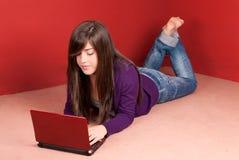 Giovane donna con il computer portatile che si trova sul pavimento nel paese Fotografia Stock