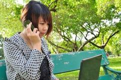 Giovane donna con il computer portatile ed il telefono cellulare Fotografie Stock Libere da Diritti
